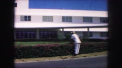1958: gardener shaping the trees in front of the hotel portico. AMES, IOWA Stock Footage