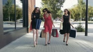 Three glamorous young women walking downtown and showing the purchases Stock Footage