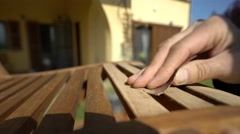 Closeup of  carpenter's hand restoring a wooden chair with sandpaper. Stock Footage