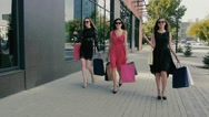 Group of attractive young women walking along shop windows. Slow motion Stock Footage