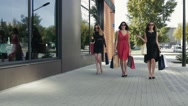 Three wonderful female friends walking down the street and talking to each other Stock Footage