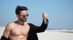 Beautiful guy sitting model looks and pours sand from hands Stock Footage