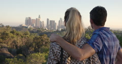 Camera moves around attractive couple as they view Los Angeles skyline 4K Stock Footage