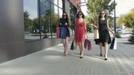 Group of attractive female friends walking in the city showing their purchases Stock Footage