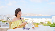 Beautiful girl on breakfast with phone at outdoor cafe with amazing view on Stock Footage
