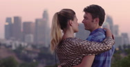 Attractive couple watching the Los Angeles skyline at dusk 4K Stock Footage