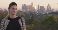 Attractive young woman stands in front of Los Angeles skyline at sunset 4K Stock Footage