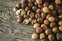 Fresh walnuts spill out of a wicker basket on autumn background on the old Stock Photos