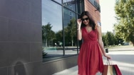 Beautiful young woman in red dress walking down the street Stock Footage