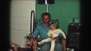1958: father holds sleeping girl while sitting in chair AMES, IOWA Stock Footage
