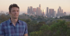 Handsome man stands in front of Los Angeles skyline in sunset light 4K Stock Footage