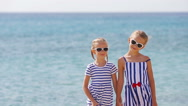 Adorable little girls ooking at camera together during beach vacation. Kids Stock Footage