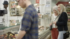 4K Senior lady & adult granddaughter shopping at deli counter in supermarket Stock Footage