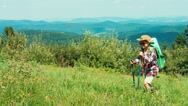 Little hiker girl going up the hill on mountains background Stock Footage