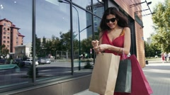 Pretty woman walking downtown and looking into her shopping bag in surprise Stock Footage