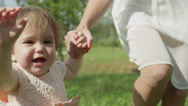 CLOSE UP SLOW MOTION: Happy baby girl walking in park, holding hands with mother Stock Footage