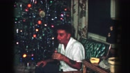 1958: a christmas tree is seen with a child opening presents AMES, IOWA Stock Footage