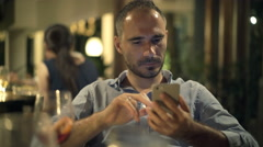 Young man sending sms, texting and drinking wine in the bar in the evening, 4K Stock Footage