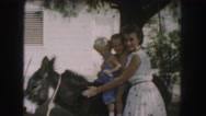 1958: women pets her donkey while her two young children sit on it  Stock Footage