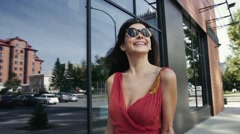 Attractive smiling woman walking down the street after. Slow motion Stock Footage