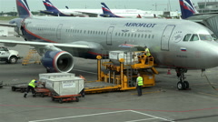 Airport workers lift containers with the luggage on board the aircraft Stock Footage