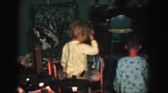 1958: children in pajamas examining their christmas gifts under the tree AMES Stock Footage