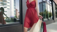Attractive young woman returning from the shopping mall with her purchases Stock Footage