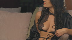 Sexy woman in erotic lace lingerie resting on the sofa indoor.Slowly Stock Footage