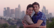 Attractive couple embrace in front of Los Angeles skyline at dusk 4K Stock Footage