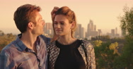 Attractive couple kiss at sunset in front of Los Angeles skyline 4K Stock Footage