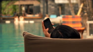 Young woman texting on smartphone lying on sunbed by swimming pool, super slow m Stock Footage