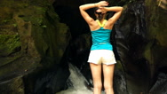 Young woman stretching arms by amazing waterfall in Bali super slow motion, 240F Stock Footage