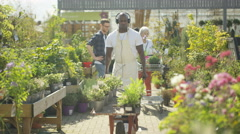4K Worker in plant nursery listening to music & dancing while customers shop Stock Footage