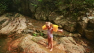 Little Girl in Arm-bands Stands Cries on Wet Stone by River Stock Footage