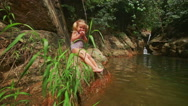Closeup Little Blond Girl Sits on Stone Bank Eats Fruit Stock Footage