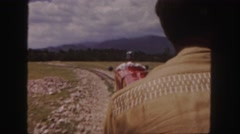 1958: a man is riding a small, red train operated by an engineer  Stock Footage