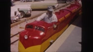 1958: red and yellow toy train pulls away from platform as lady walks  Stock Footage