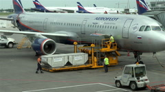 Airport workers in overalls containers are loaded with luggage on the plane Stock Footage