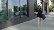 Pretty woman walking down the street and adjusting her sunglasses. Slow motion Stock Footage