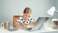Schoolgirl eating chocolate sitting at the desk in the evening and looking Stock Footage