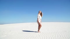 Beautiful girl in a white dress standing in the desert Stock Footage
