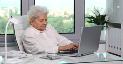 Retired Caucasian Old Woman Using Computer Device and Introducing Finances Data Stock Footage