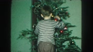 1958: boy decorating the christmas tree during the holidays AMES, IOWA Stock Footage