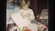 1958: a little girl in living room at christmas receive a red and white dress. Stock Footage