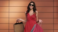 Fair-skinned young woman waves her shopping bags Stock Footage