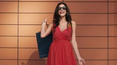 Beautiful brunette with shopping bags against orange background Stock Footage