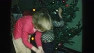 1958: brother and sister decorating the family christmas tree AMES, IOWA Stock Footage