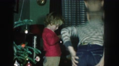 1958: siblings are seen on a table posing beside a christmas tree AMES, IOWA Stock Footage