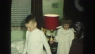 1958: kids in pajamas opening gifts from under a christmas tree AMES, IOWA Stock Footage