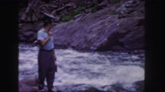 1958: a man standing along a powerful river sees something across the way Stock Footage